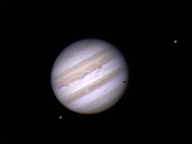 Jupiter with Europa casting a shadow and Io.